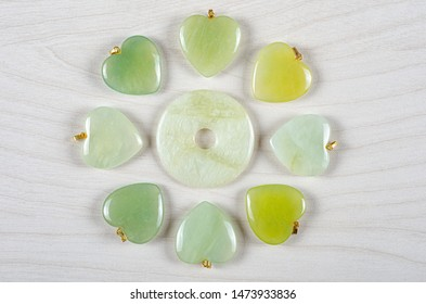 Butter jade donut surrounded by six hearts of same stone few different tones. Top view on white wooden background