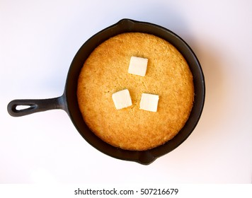 Butter melting on hot cornbread that was cooked in a black cast iron skillet isolated on white
