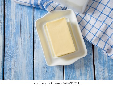 butter on butter dish on blue wooden surface