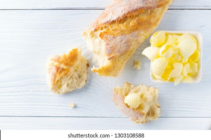 Butter on a fresh crunchy homemade Bread. Butter Rolls. Healthy organic Breakfast on white wooden table. Top view. Rustic still-life.