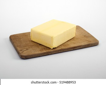 Butter on wooden chopping board, white background