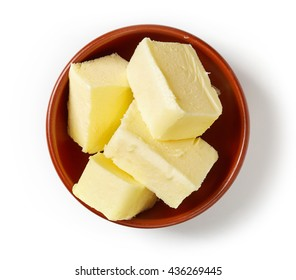 Butter pieces in clay bowl isolated on white background, top view