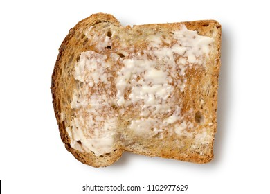 Butter spread on a single slice of whole wheat toast isolated on white from above.