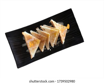 Butter toast topped with sweetened condensed milk on a black plate with clipping path.