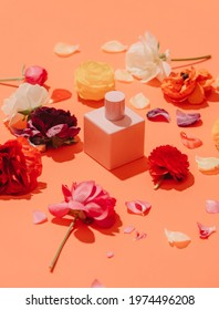 buttercup flowers and perfume bottle on orange background. Above view