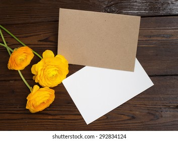 Buttercups flowers and white paper on wooden background.