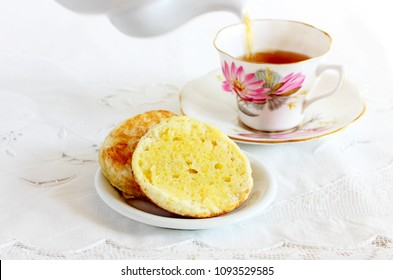 Buttered English muffins served with breakfast tea