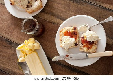 Buttered fruity rock cakes with jam and whipped cream served on a plate with a knife in an overhead view