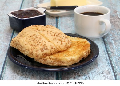 A buttered and grilled hard roll with coffee and condiments for breakfast.