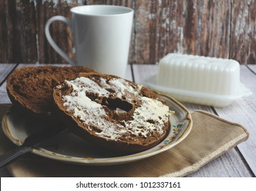 A buttered pumpernickel bagel on a plate sitting on wood surface with a white coffe mug and wood background.