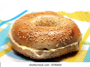Buttered sesame seed bagel on cloth mat