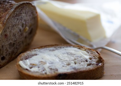 A buttered slice of cranberry walnut bread