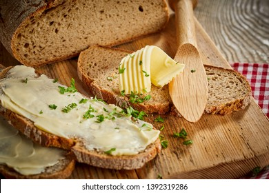 Buttered slices of fresh rye bread topped with chopped parsley and a decorative twist or curl of butter on a wooden board with spreader or butter knife