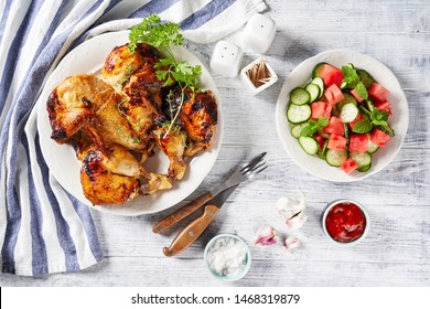 Butterflied grilled chicken al mattone on a white plate with ketchup, on a wooden table with a salad of cucumber, watermelon, and mint with ingredients on a cutting board, view from above, close-up