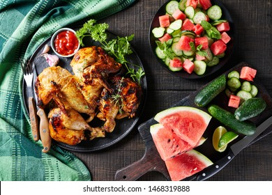 Butterflied grilled chicken on a black plate with ketchup, parsley, thyme, on a wooden table with a summer salad of cucumber, watermelon, and mint with ingredients on a cutting board, flat lay