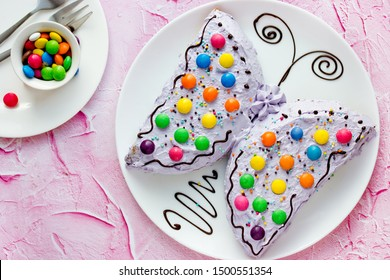 Butterfly cake - delicious homemade cake shaped colorful butterfly decorated with cream, chocolate and colored candies