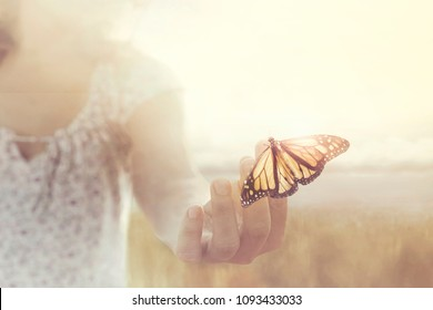 a butterfly leans on a hand of a girl in the middle of nature