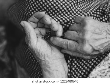Butterfly on hand of elderly woman. Toned image. Selective focus