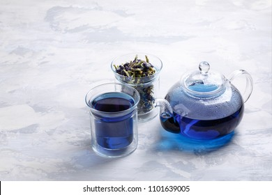 Butterfly pea flower tea is brewed in a glass teapot and served into a transparent cup. Blue herbal tea.