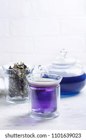 Butterfly pea flower tea is brewed in a glass teapot and served with lemon into a transparent cup. Blue herbal tea.