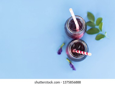 Butterfly pea juce in grass bottle with leaf and flower on light blue background, herb dink for healthy concept