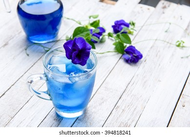 Butterfly pea juice with ice in trasparent cup serve on wooden table with flower.