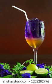Butterfly pea juice mix honey and lime with soda water with ice on wooden table / select focus