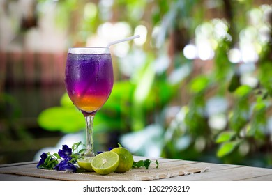 Butterfly pea juice mix honey and lime with soda water with ice on the bamboo mat and wooden table in green garden / Blurred and select focus and space for texts