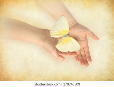 Butterfly releasing from woman's hands.