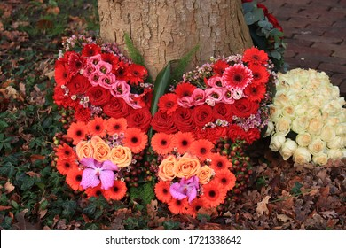 Butterfly shaped sympathy flowers near a tree at a cemetery