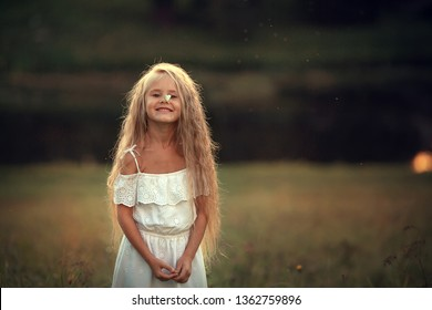A butterfly is sitting on a nose of beautiful long-haired girl. Image with selective focus and toning.