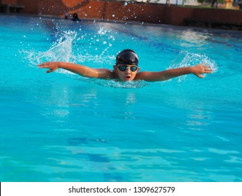 Butterfly stroke by young boy. He put speed in his position.