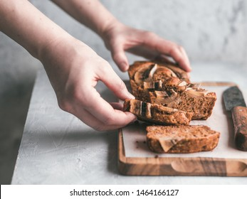 Butter-free,sugar-free banana bread with oat flour,soft curd cheese,honey. Woman hand with slice of banana bread on gray table. Ideas recipe healthy diet breakfast. Selective focus