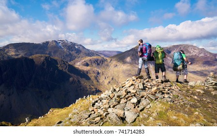 BUTTERMERE, LAKE DISTRICT, ENGLAND, UK - APRIL 09, 2016: Three hikers looking out over the summits of High Crag from the summit of Fleetwith Pike, English Lake District.
