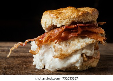 Buttermilk biscuit and fried chicken breast sandwich with a fried egg and bacon on dark rustic background