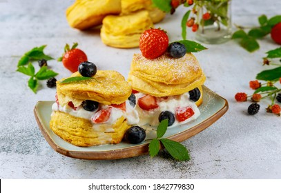 Buttermilk biscuit in plate with berries on white background.