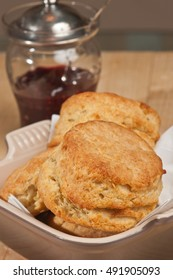 Buttermilk biscuits in a white bowl with a glass jay of jam with a silver cover and spoon on a wood cutting board