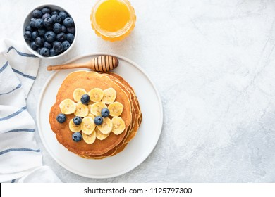 Buttermilk Pancakes with banana, blueberries and honey on concrete background. Top view and copy space for text. Top view of pancakes with berries on table