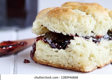 Buttermilk southern biscuit with raspberry or strawberry jam or jelly. Extreme shallow depth of field with selective focus on jam..