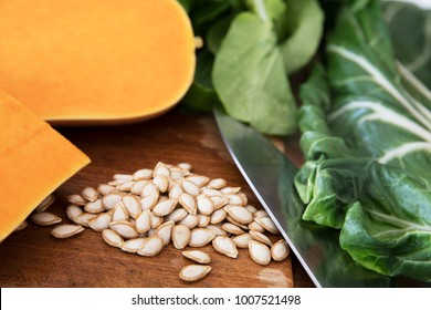 Butternut squash seeds on a cutting board with a knife, pieces of butternut squash and chard.