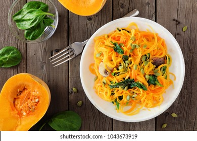 Butternut squash spirilized noodles with spinach and pumpkin seeds on dark wood background, Healthy eating concept. Top view, table scene.