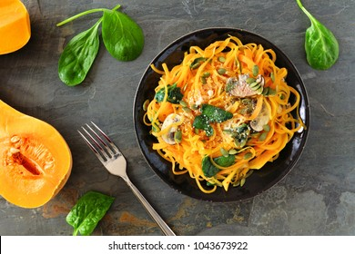 Butternut squash spirilized noodles with spinach and pumpkin seeds on dark slate background, Healthy eating concept. Top view, table scene.