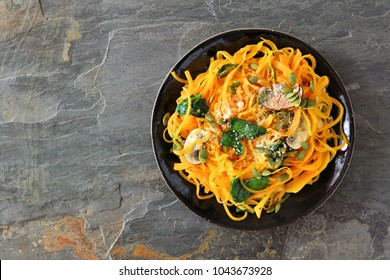 Butternut squash spirilized noodles with spinach and pumpkin seeds on dark slate background, Healthy eating concept. Top view.