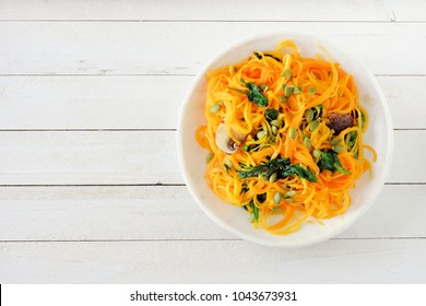 Butternut squash spirilized noodles with spinach and pumpkin seeds on white wood background, Healthy eating concept. Top view.