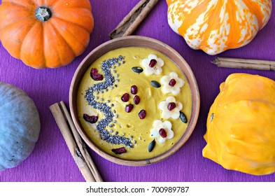 Butternut squash and turmeric smoothie bowl topped with banana, pomegranate, pumpkin kernels, chia, hemp seeds and dried cherries. Wooden bowl, purple background. Top view.