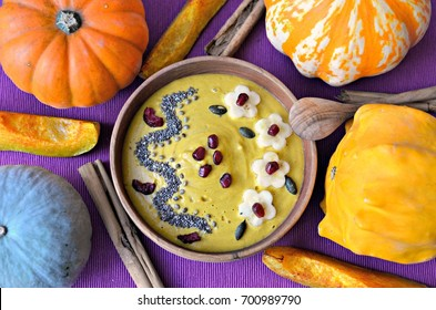 Butternut squash and turmeric smoothie bowl topped with banana, pomegranate, pumpkin kernels, chia, hemp seeds and dried cherries. Wooden bowl and spoon, purple background. Top view.