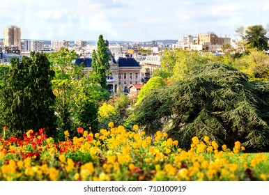 Buttes Chaumont park in Paris - one of the biggest parisian gardens situated in the XIXth district of the french capital. View from the hills on the garden and the city beyond..