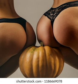 Buttocks ass and pumpkin close-up. Pumpkin ass. Sexy Halloween art design. Pumpkins isolated on girl with big bum. Trick or treat. Pumpkin head jack lantern. Carved Pumpkin - funny concept