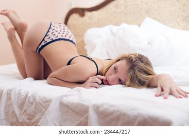 buttocks up beauty: image of beautiful blond sexy young woman on white bed copy space background