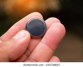 Button battery in hand on  blurred background